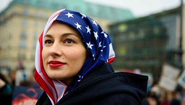 Kobieta w hidżabie z flagi USA podczas protestów w Berlinie. - Sputnik Polska