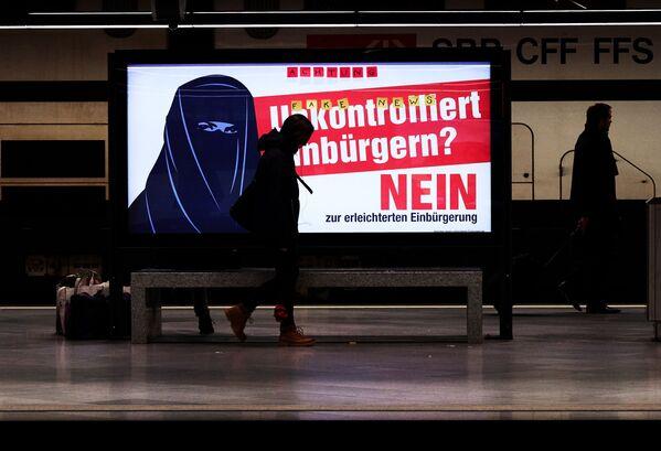 Plakat wyborczy przedstawiający kobietę w burcę na ulicy w Zurychu. - Sputnik Polska