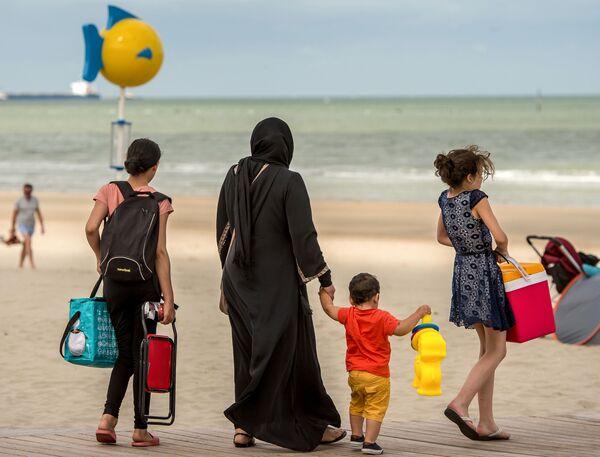 Muzułmanka w hidżabie z dziećmi na plaży na północy Francji. - Sputnik Polska