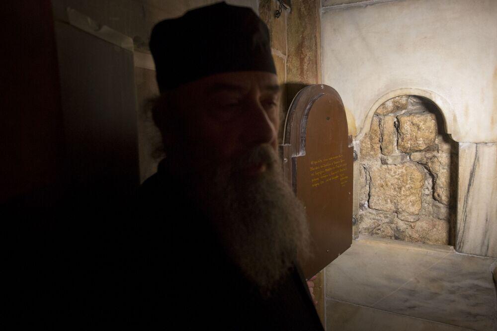 Grecki ksiądz stoi przy oknie, przez które widać mur kamiennej jaskini, w której został pochowany Jezus Chrystus.