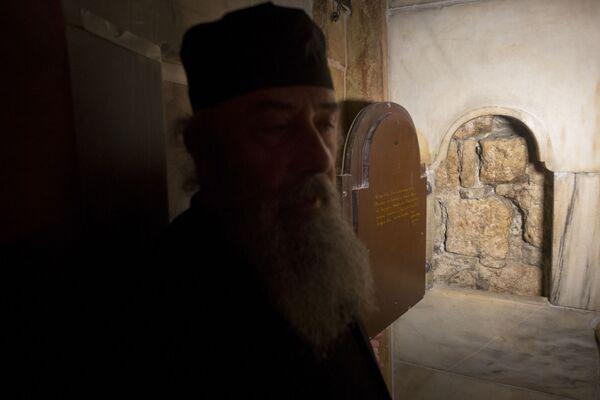Grecki ksiądz stoi przy oknie, przez które widać mur kamiennej jaskini, w której został pochowany Jezus Chrystus. - Sputnik Polska