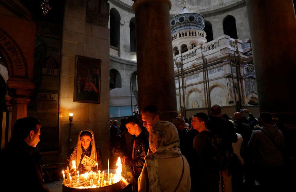 Wierni zapalają świece w odrestaurowanej Kuwukli w Świątyni Grobu Pańskiego.