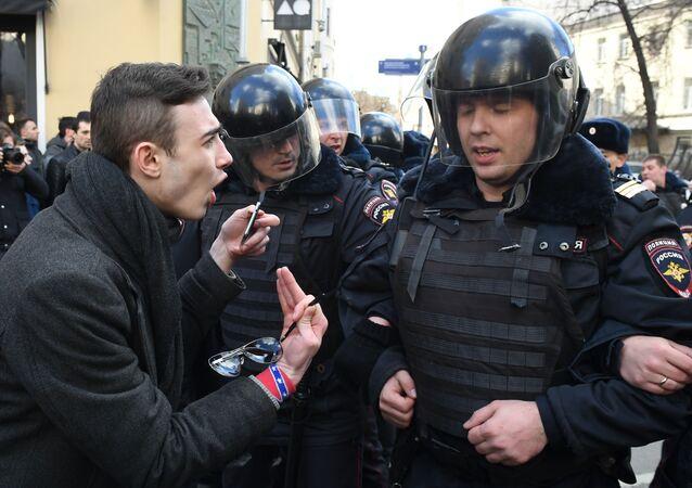 Policjanci i uczestnik nielegalnego wiecu na Placu Puszkina w Moskwie