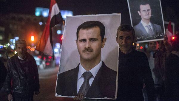 Mieszkańcy Damaszku trzymają w rękach portret syryjskiego prezydenta Baszara Asada - Sputnik Polska