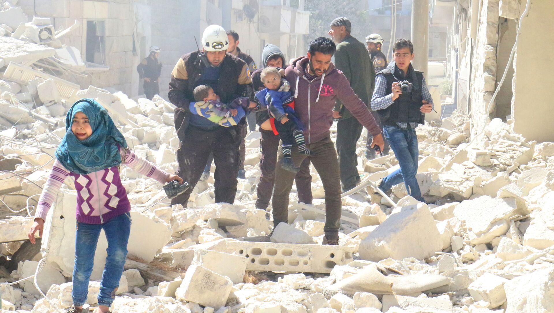 Wolontariusze Białych Hełmów i mieszkańcy szukają rannych w wyniku ataków na niekontrolowane przez syryjski rząd miasto Idlib - Sputnik Polska, 1920, 15.06.2021