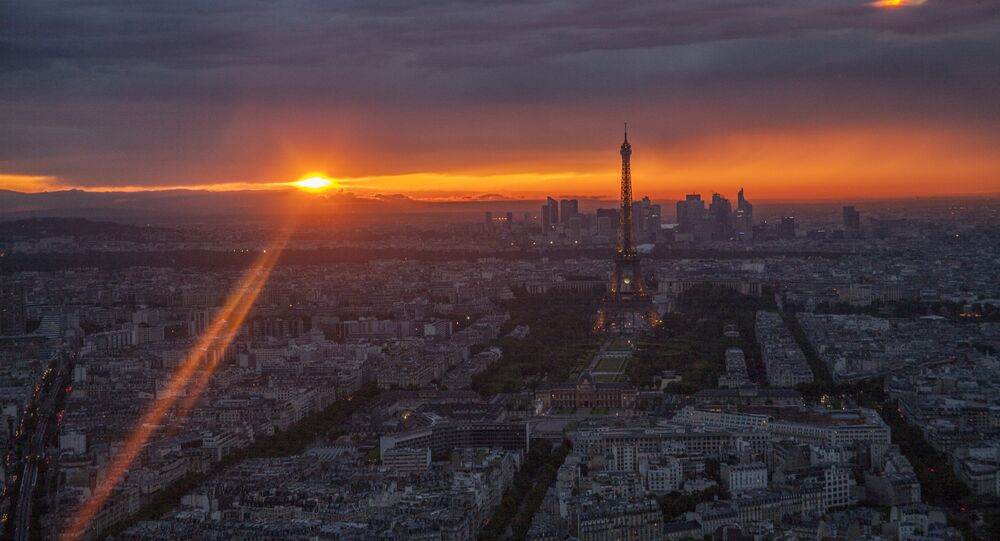 Sunset, the Eiffel Tower and Paris looking west from the Ciel de Paris restaurant atop Tour Montparnasse, during a brief moment of sunset between rain storms.