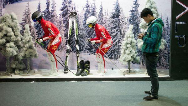 Człowiek ze smartphonem przed witryną sklepu z odzieżą narciarską w Pekinie - Sputnik Polska
