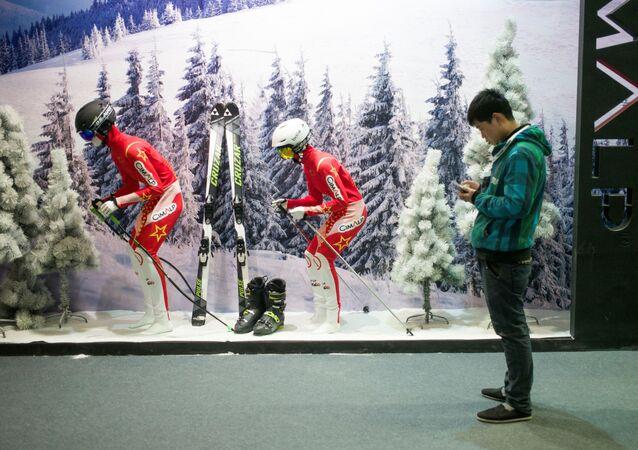 Człowiek ze smartphonem przed witryną sklepu z odzieżą narciarską w Pekinie
