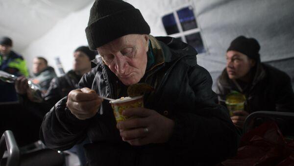 Mężczyzna je obiad w punkcie dla bezdomnych  - Sputnik Polska