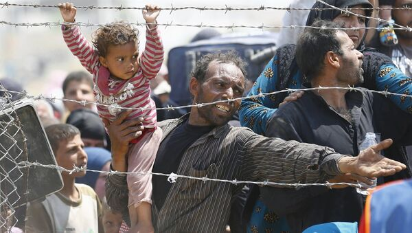 Syryjski uchodźca z córką na rękach na granicy z Turcją - Sputnik Polska
