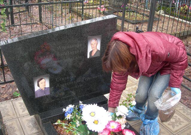 Jelena Atamanczuk, potomkini czerwonoarmisty Wasilija Semionowa, rozsypuje ziemię na grobie jego matki. Obwód kałuski
