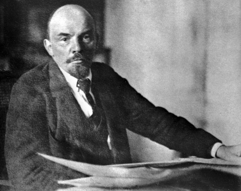 Władimir Lenin w swoim gabinecie na Kremlu w zwyczajnym, jak mogłoby się wydawać, z lekka workowatym garnitirze, w zwyczajnej białej koszuli, z prostym krawatem. Jednak w 1920 roku białych koszul i garniturów nie było w żadnej  innej garderobie.