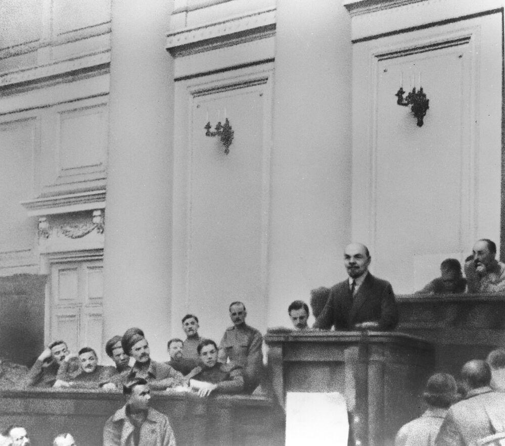 """Władimir Lenin występuje w sali posiedzeń Pałacu Taurydzkiego z Tezami kwietniowymi. W każdych warunkach Władimir Lenin dbał o swoje ubranie. Jakby już wtedy planował stać się """"przykładem dla wszystkich pionierów"""", jakim uczyniły go liczne opowieści i wspomnienia."""
