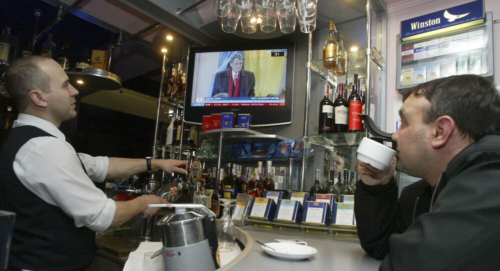 Gość i barman oglądają ukraińską telewizję w Doniecku