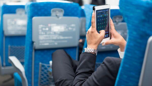 Biznesmen z telefonem w ręku w samolocie - Sputnik Polska