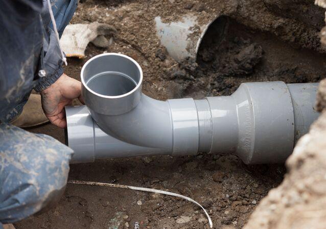 Robotnik i rura kanalizacyjna