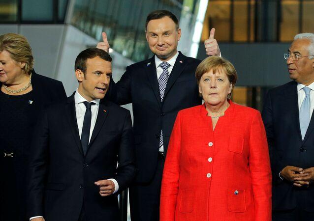 Prezydent Polski Andrzej Duda z uniesionymi kciukami na zdjęciu ze szczytu NATO w Brukseli.