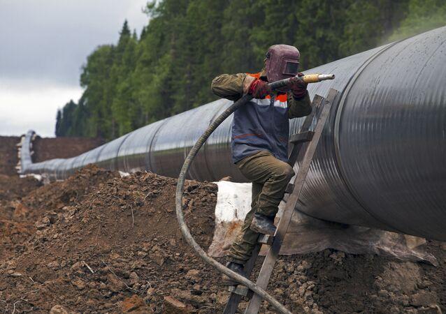 Robotnik czyści złączenia gazociągu