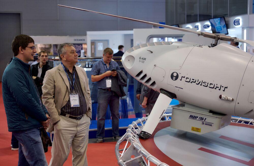 """Goście oglądają bezzałogowy statek powietrzny """"Horyzont""""na Międzynarodowym Salonie Morskiej Techniki Wojskowej w Sankt Petersburgu"""
