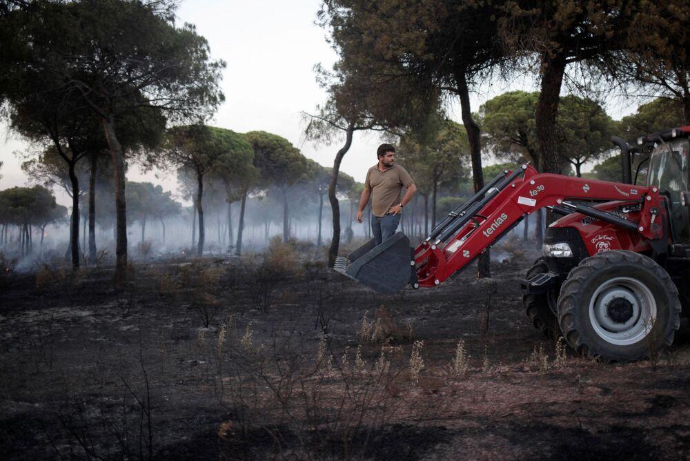 Mężczyzna na traktorze pomaga gasić pożar lasu na południu Hiszpanii
