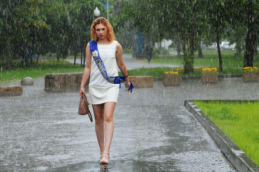 Absolwentka idzie po ulicy Moskwy podczas ulewy.