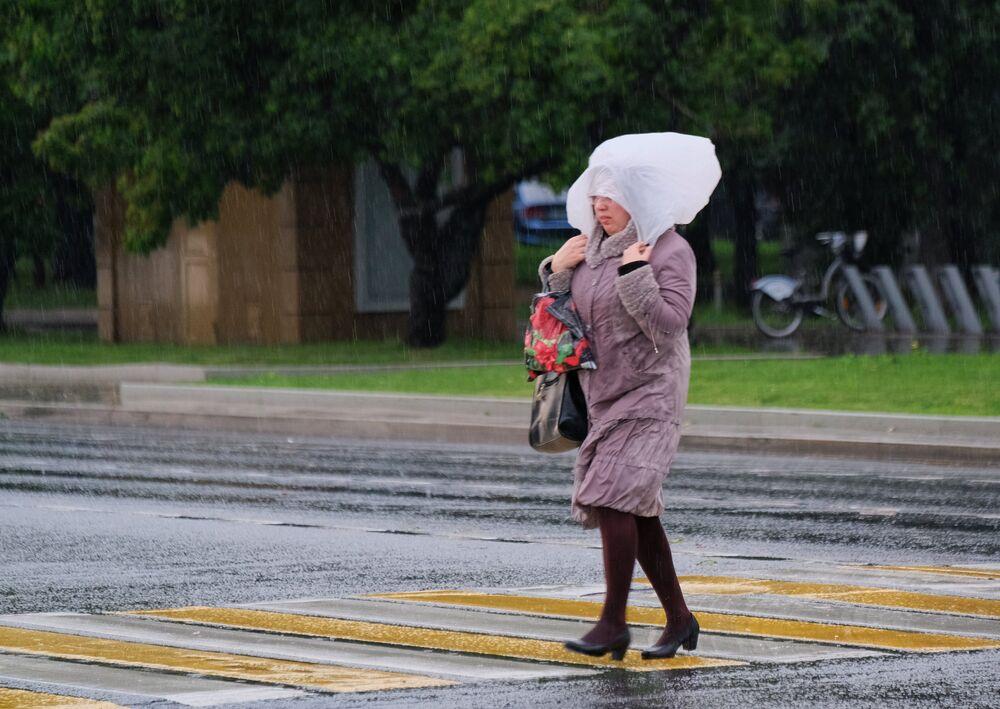 Kobieta idzie po ulicy Moskwy podczas ulewy.