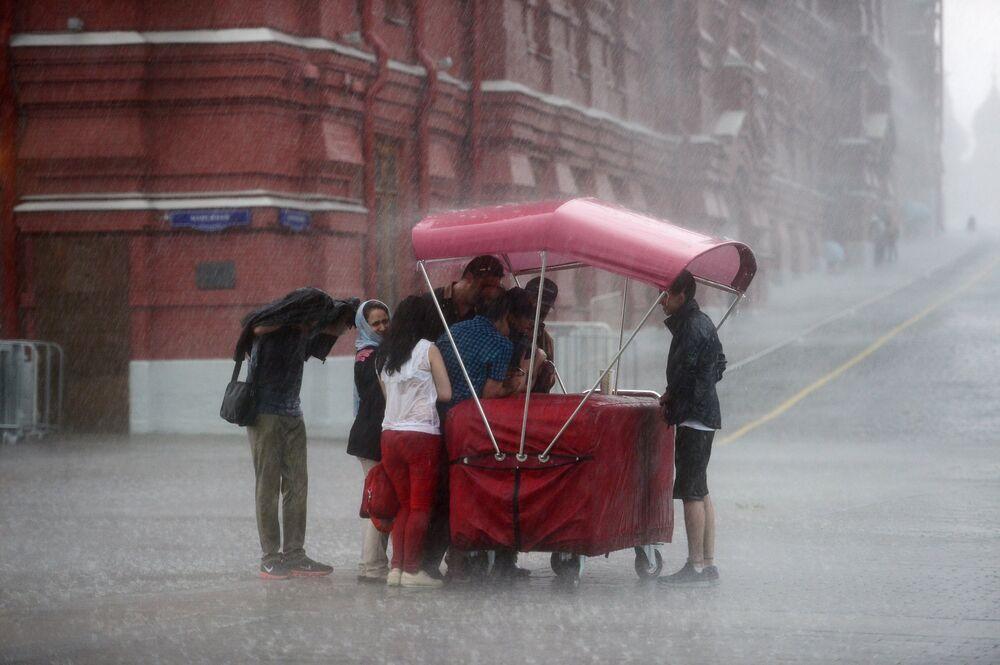 Przechodnie podczas ulewy przy Placu Czerwonym w Moskwie.