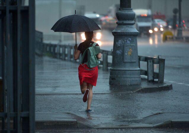 Dziewczyna biegnie z parasolem podczas deszczu w Moskwie