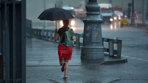Dziewczyna biegnie z parasolem podczas deszczu w Moskwie - Sputnik Polska