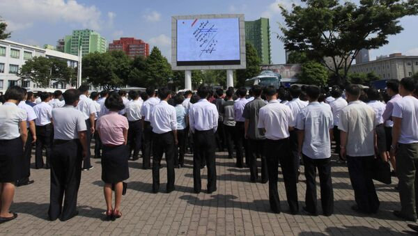 Mieszkańcy na stacji w Pjongjangu podczas oglądania wiadomości o rozpoczęciu wystrzału pocisków balistycznych w Korei Północnej - Sputnik Polska