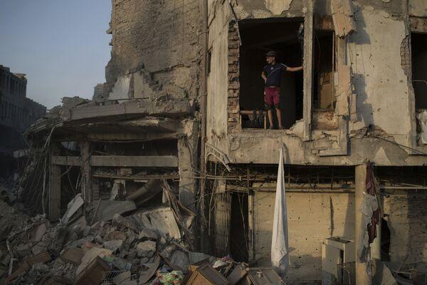 Oficer federalnej policji Iraku stoi w zniszczonym budynku w Mosulu - Sputnik Polska