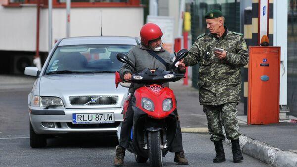 Funkcjonariusz ukraińskiej straży granicznej sprawdza dokumenty - Sputnik Polska