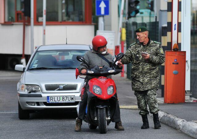 Funkcjonariusz ukraińskiej straży granicznej sprawdza dokumenty