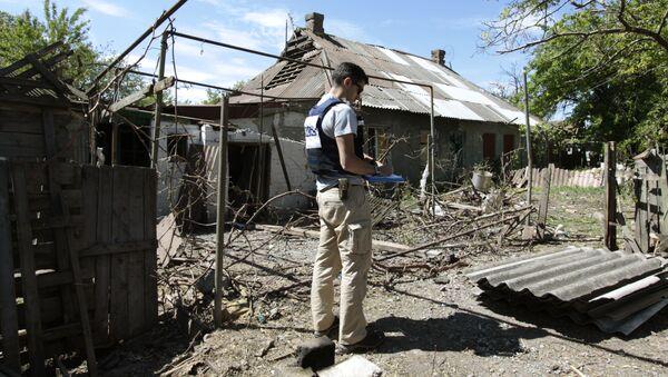 Pracownik OBWE przy domie mieszkalnym, który uległ ostrzałowi. Obwód doniecki - Sputnik Polska