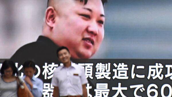 Piesi mijają ogromny ekran z wizerunkiem północnokoreańskiego przywódcy Kim Dzong Una w Tokio - Sputnik Polska