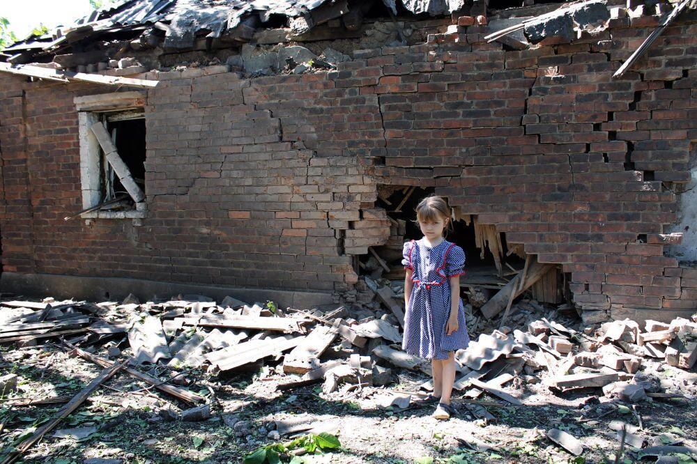 Dziewczynka przy zburzonym domu w Gorłowce