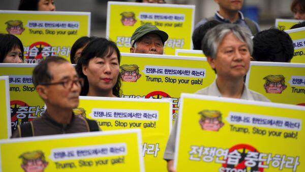 Mieszkańcy Korei Południowej protestujący w pobliżu ambasady USA w Seulu przeciwko ćwiczeniom wojskowym Korei Południowej i USA UFG - Sputnik Polska