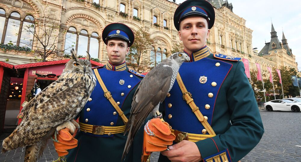 Żołnierze słuzby ornitologicznej Kremla z ptakami na Placu Czerwonym w Moskwie