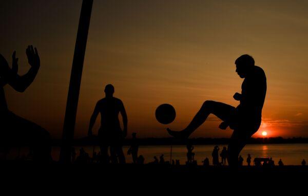 Odpoczywający ludzie grają w piłkę nożną na plaży nad brzegiem Wołgi w Samarze. - Sputnik Polska