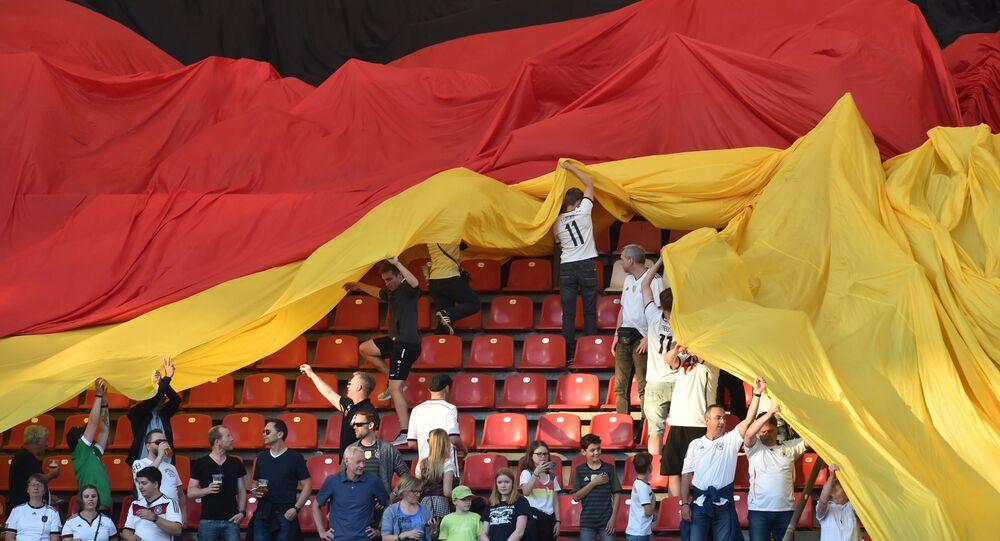 Kibice z ogromną flagą Niemiec na meczu piłki nożnej