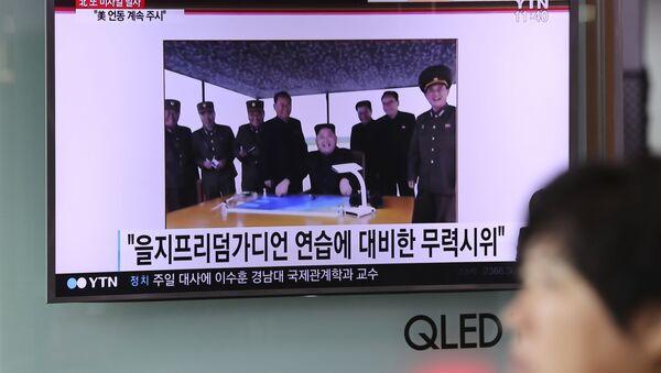 Program informacyjny o kolejnym starcie północnokoreańskich rakiet na ekranie telewizora na dworcu w Seulu - Sputnik Polska