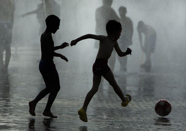 Dzieci grają w piłkę koło fontanny, Madryt, Hiszpania