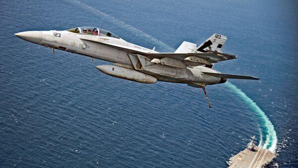 Amerykański myśliwiec bombowy F/A-18F Super Hornet leci nad lotniskowcem USS Gerald R. Ford - Sputnik Polska