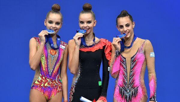 Gimnastyczki Arina Awerina, Dina Awerina i Lina Aszram podczas ceremonii rozdania nagród w mistrzostwach świata w gimnastyce w Pesaro. - Sputnik Polska