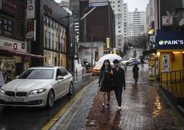 Mieszkańcy miasta z parasolem na jednej z ulic w Seulu