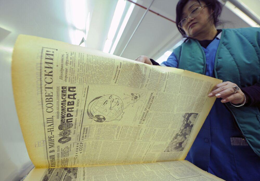 Pracownik fundacji Rosyjskiej Biblioteki Państwowej prezentuje gazetę Komsomolskaja Prawda z 6 października 1957