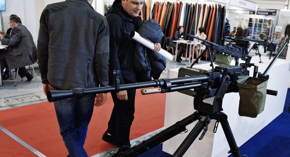 Mężczyzna przygląda się karabinowi na wystawie Broń i bezpieczeństwo w Kijowie
