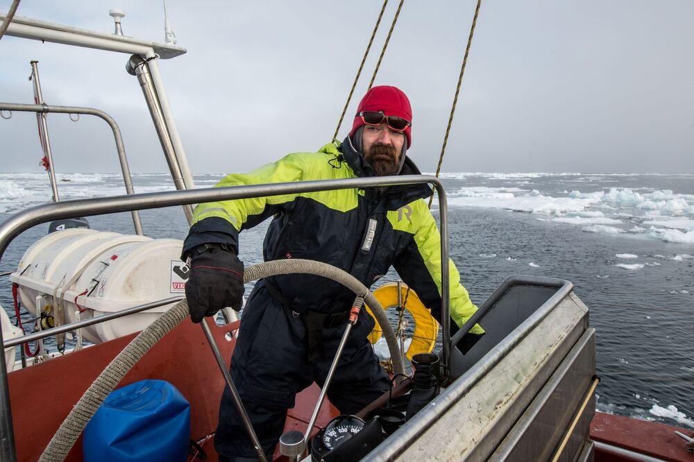 Żeglarz polarny Andriej Simonienkow kieruje jachtem przy brzegu jednej z wysp wchodzącej w skład archipelagu Ziemia Franciszka Józefa.