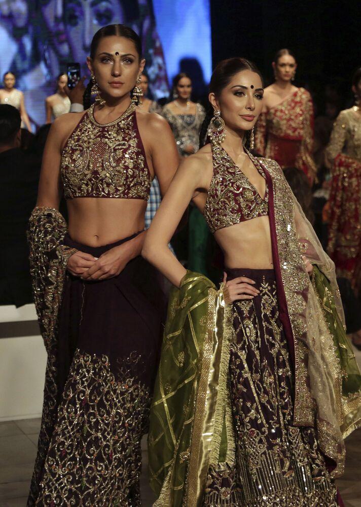 Modelki prezentują kolekcję projektanta Shamsha Hashwani podczas Tygodnia mody ślubnej w Pakistanie