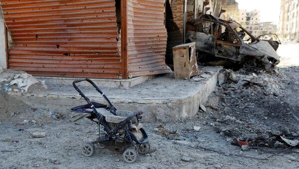 Wózek dla dziecka obok spalonego samochodu w Rakce - Sputnik Polska